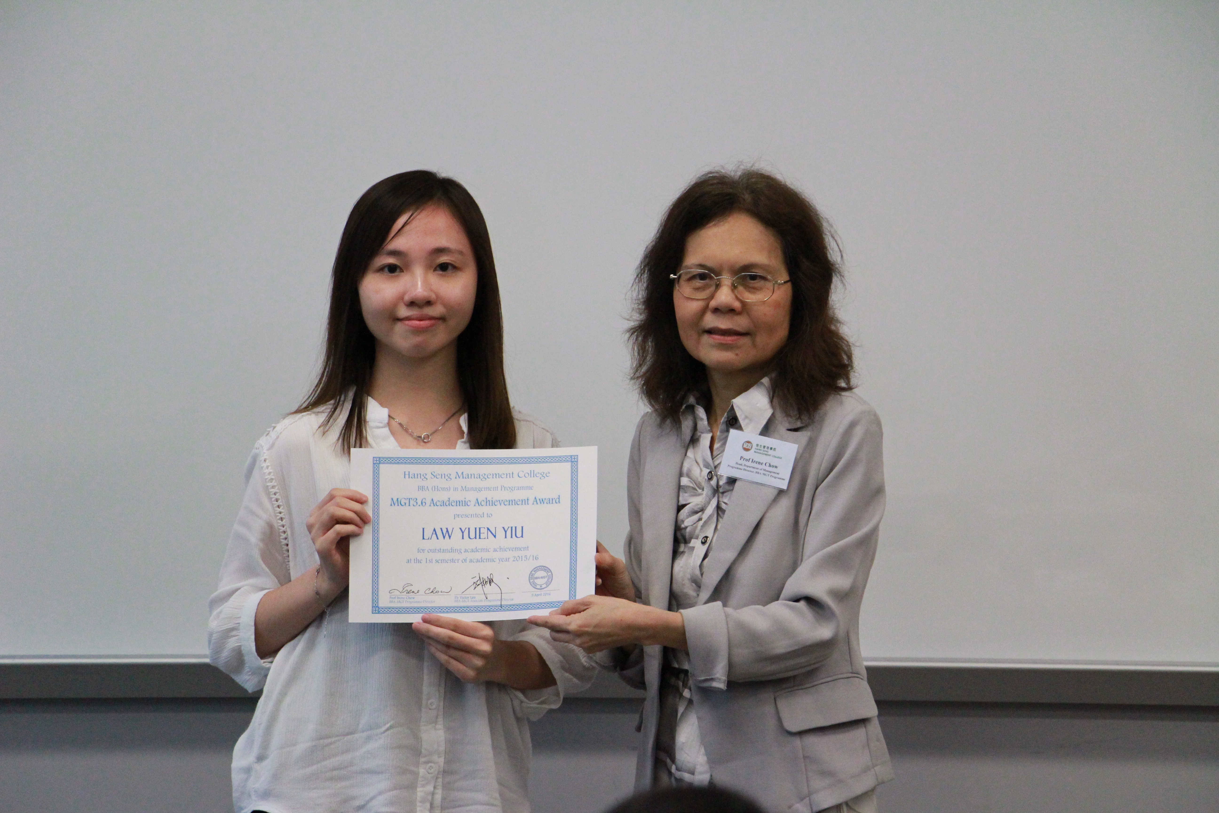 Prof. Chow presents the certificate to the student.
